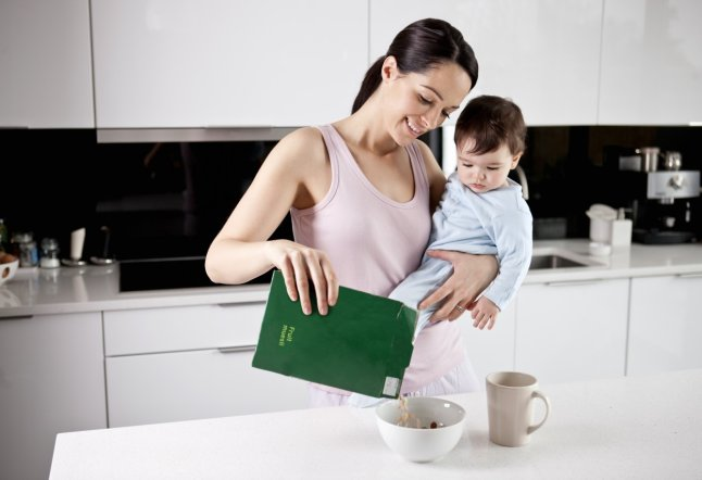 Young mother holding her baby son whilst making breakfast