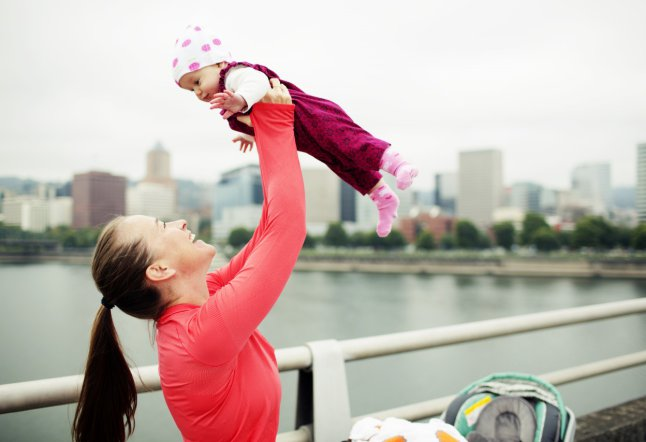 Running mom playfully lifting baby up on city bridge