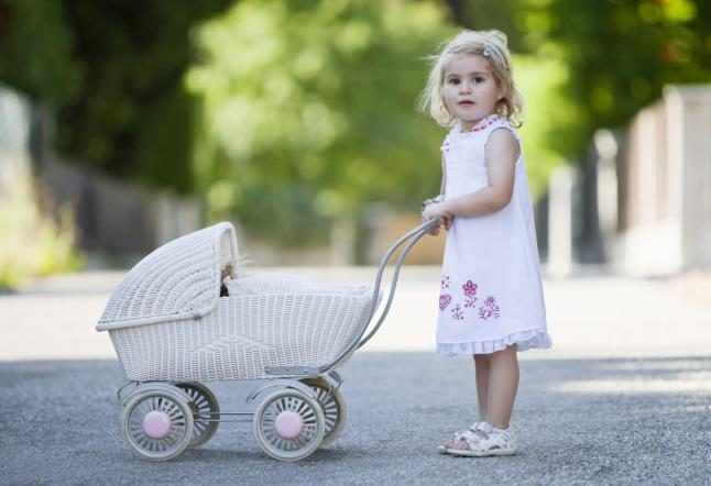 Germany Bavaria Girl (2-3) playing with toy baby carriage