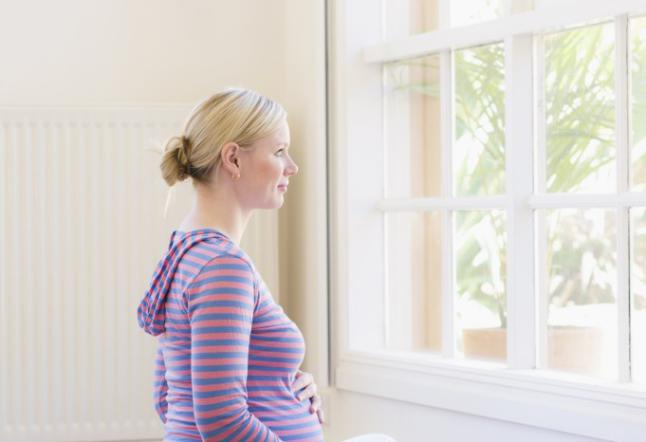 Pregnant woman sitting at window