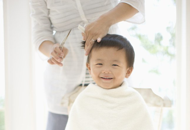 Baby boy having hair cut by mother