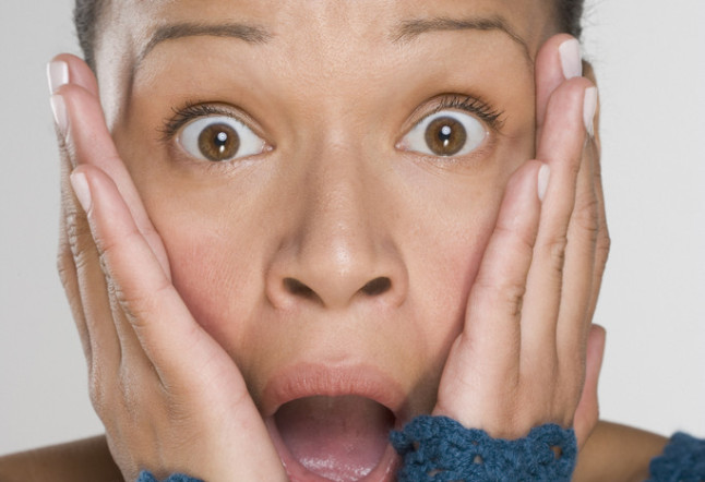 Portrait of surprised woman with hands on face