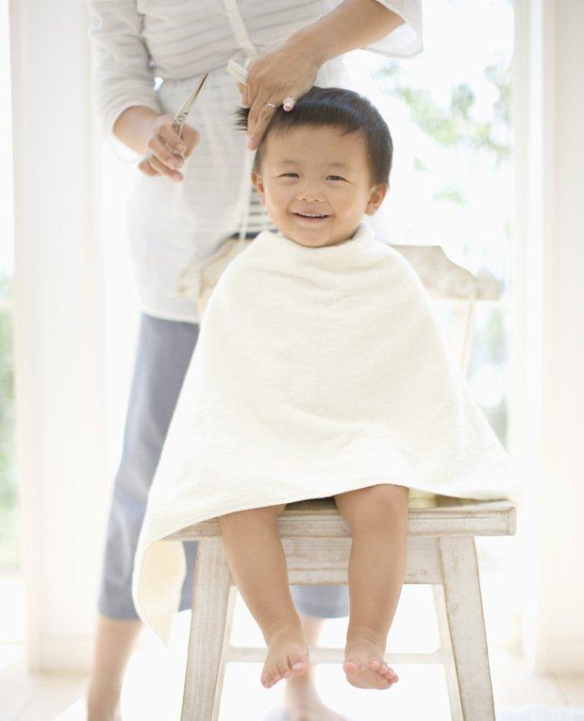 Baby boy having hair cut by mother