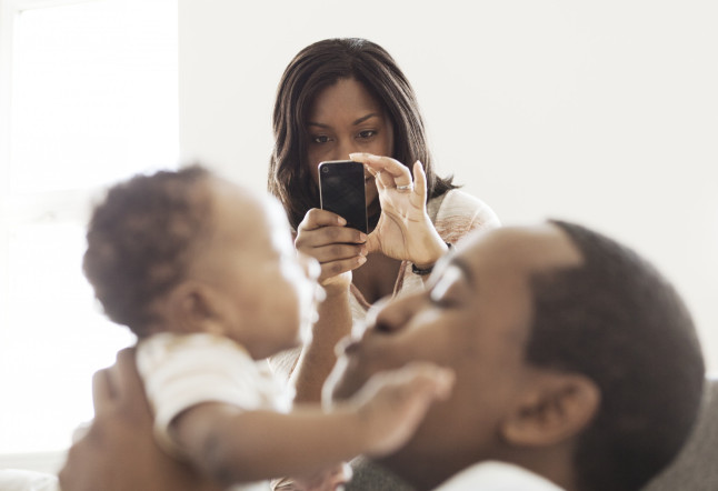 Mother taking photo of father playing with baby son (2-5 months)