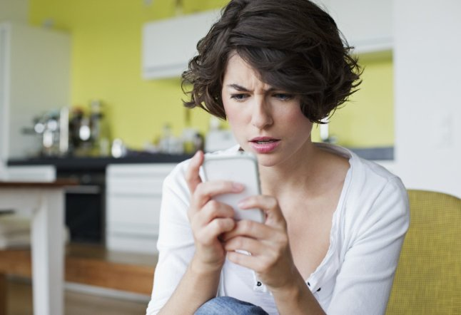 Young woman in domestic kitchen text messaging