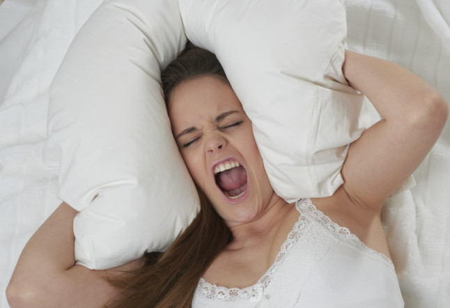 Woman lying on bed and screaming